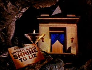 """Auschnitt aus Jackson Video Leave me Alone. Unten links auf einer Zeitung eine Schlagzeile """"Michael builds a shrine to Liz"""". Dahinter die Pfeiler eines Theaters mit einem blauen, offenem Vorhang. Darüber eine sich drehende Pyramide."""
