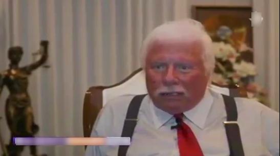 Älterer Mann, weiße Haare, Hosenträger, hinter dem Schreibtisch